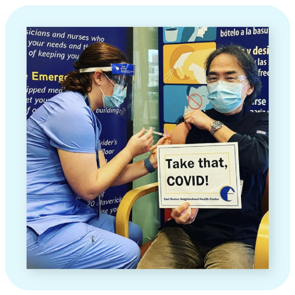 man wearing a mask receiving a vaccine at ebnhc