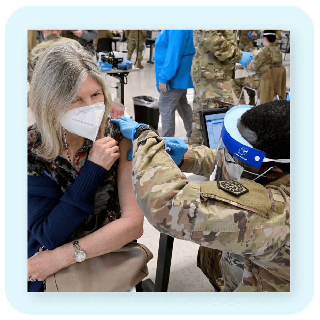 woman wearing a mask receiving a vaccine